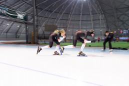 Simon Aannø og Sofie Ulset trener på skøyteløp med trener AG i bakgrunnen
