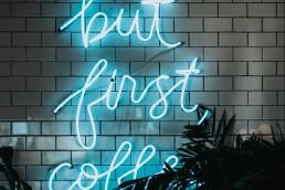 Lysende tekst av ordene but first coffee. Foto.