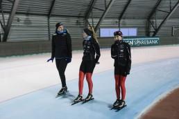 Ida Njåtun trener på isen sammen med to jenter