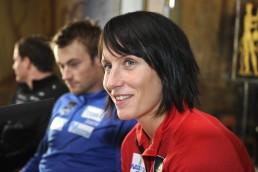 Marit Bjørgen smiler med Petter Northug i bakgrunnen