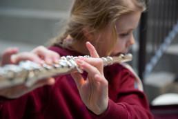 Jente spiller tverrfløyte. Foto.