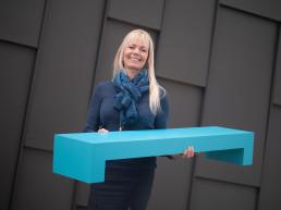 Elisabeth Vik med en blå klamme-figur i hånda som symboliserer logoen til banken. Foto.