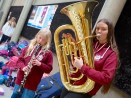 Blond jente spiller klarinett og mørkhåret jente spiller tuba. Foto.