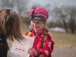 Liten jente i russedress viser frem et ark til voksen dame. Foto.