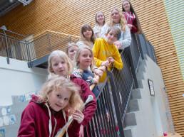 Ni barn står lent inntil rekkverk oppover en trapp. Foto.