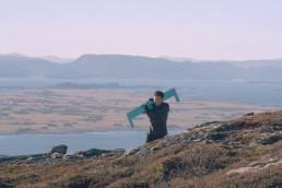 Foto av Wenche Olden Gilde som går opp fjellet Kopparen med ny logo på skuldrene