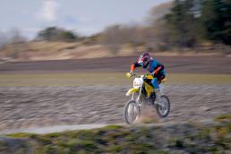 Motorsykkel i fart på motocrossbane. Person med hjelm sitter på setet. Foto.