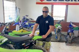 Person med solbriller og skjegg står ved siden av flere motorsykler i garasje og smiler til kamera. Foto.