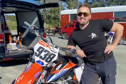 Mann med solbriller lener seg inntil motorsykkel og smiler til kamera. Foto.