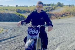 Mann med solbriller sitter på motorsykkel og ser i kamera. Foto.