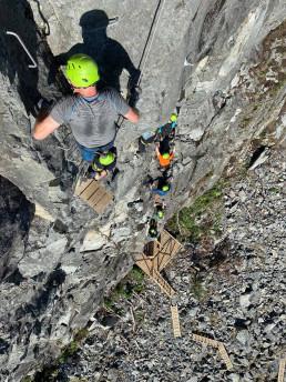 Foto av ferrata-klatrere i fjellveggen