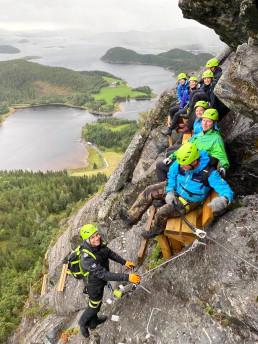 Fot av mange ferrata-klatrere i fjellveggen som tar en pause på krakk